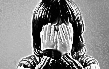 Niño triste tapando su cara